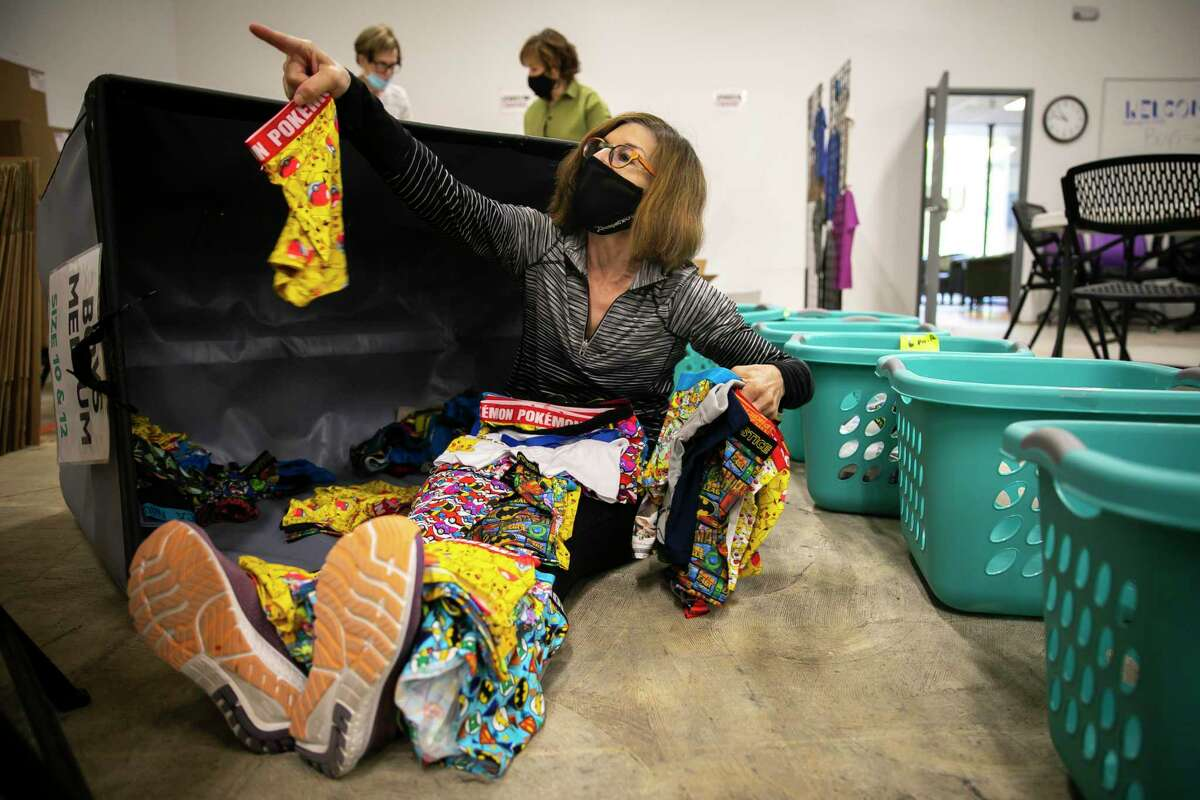 Volunteer Karen Robbins sorts and counts stacks of brand-new pairs of underwear at the Undies for Everyone headquarters in the Willowbend neighborhood of Houston.