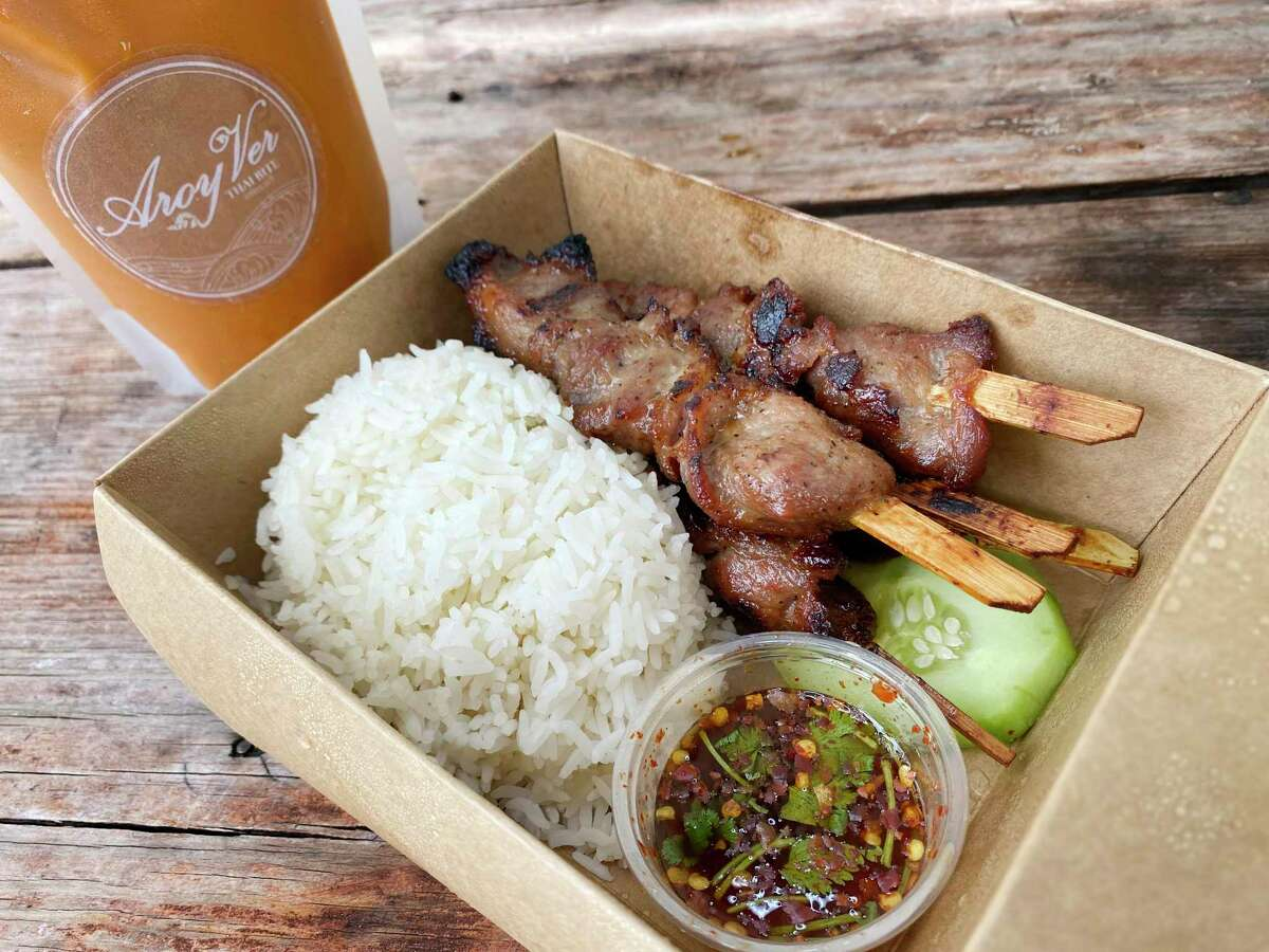 Grilled pork skewers called moo ping come with rice and Thai chile sauce, and Thai tea is served in a sealed bag like a juice pouch at Aroy Ver, a Thai food trailer parked on Broadway north of the Pearl at Broadway News.