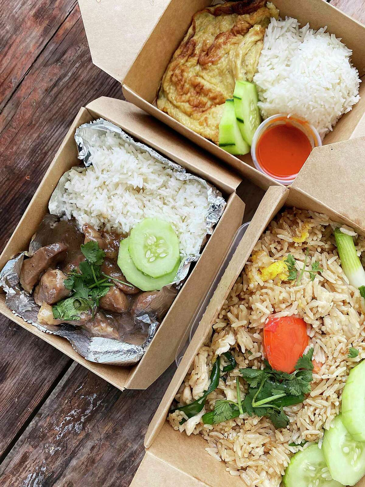 The menu includes moo wan sweet pork, left, a khai jiao Thai omelet and khao pad fried rice with chicken at Aroy Ver, a Thai food trailer parked on Broadway north of the Pearl at Broadway News.