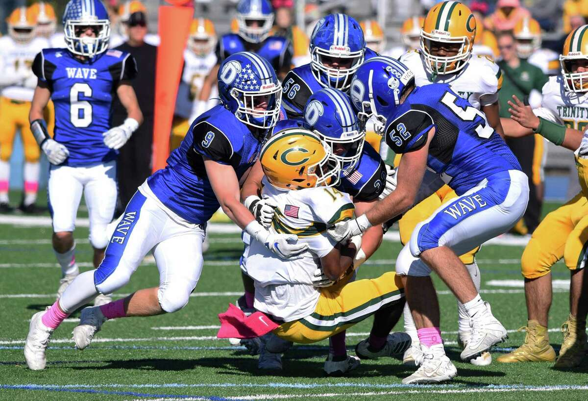 The Darien defense, including Sam Wilson (9), David Evanchick (33) and Will Bothwell (52) tackle Trinity Catholic's Branden Louis (14) during a football game at Darien High School on Saturday, Oct. 19, 2019.