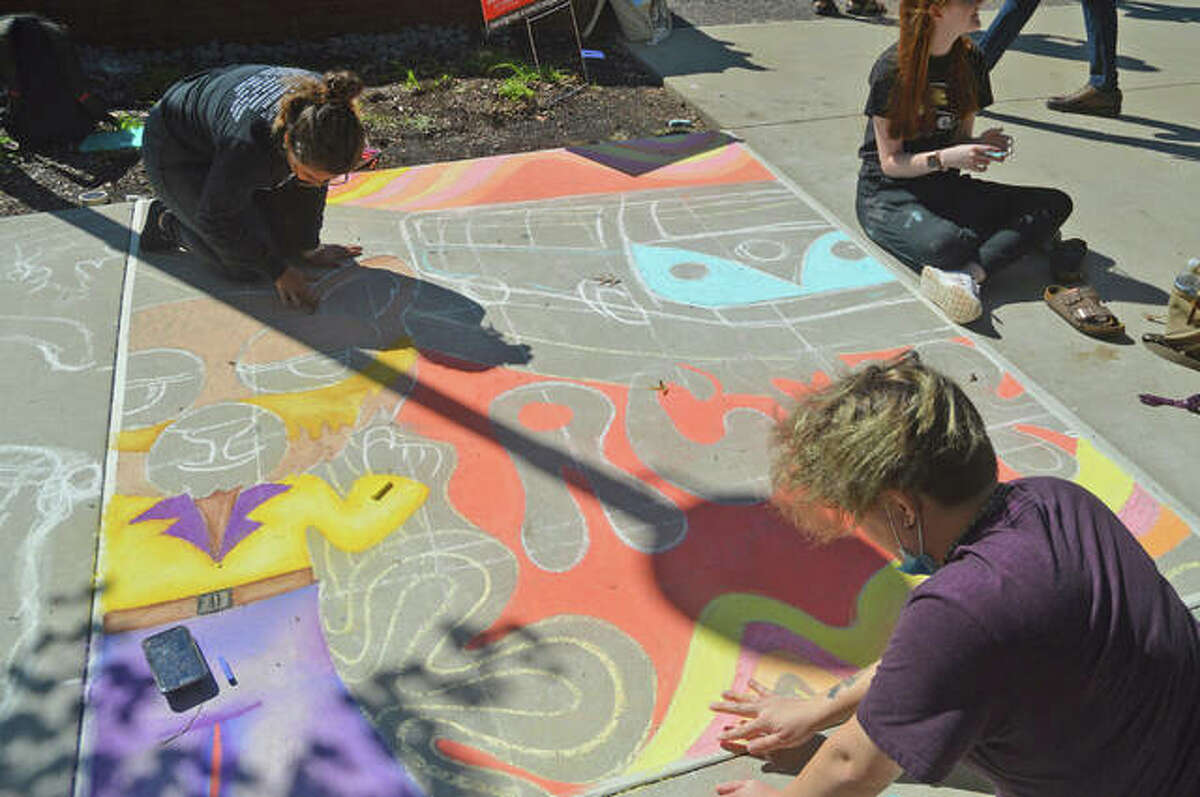 Students from Revolution Campus Ministry at SIUE work on their mural during Wednesday's Chalk Mural Contest at Stratton Quad. The event is part of SIUE's Homecoming week.