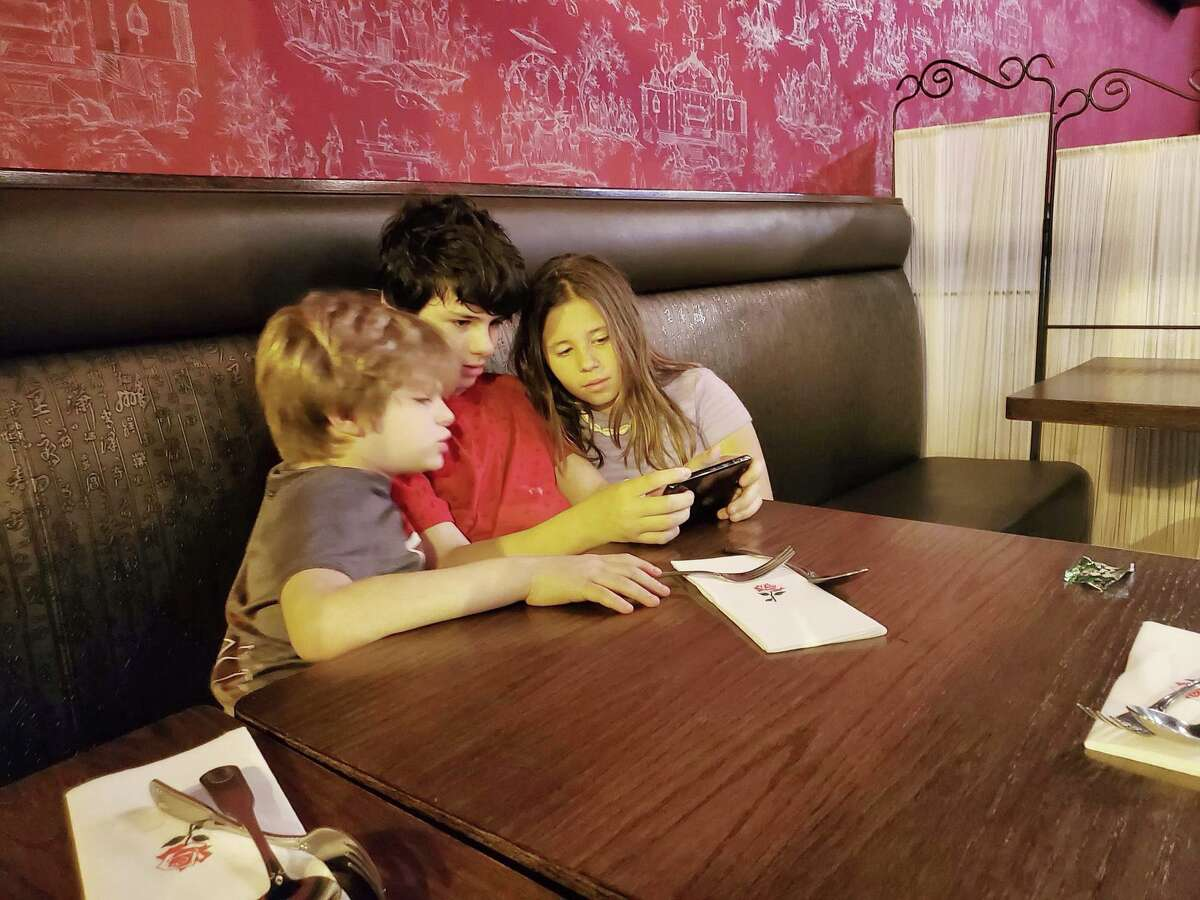 Claire Tisne Haft's children - George, 10, Louis, 13, and Selma, 12 - peer at a screen.
