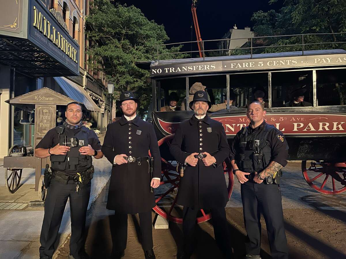 """Logan Haynes, second from left, with another extra and two real police officers pose on the set of HBO's """"The Gilded Age"""" in Troy."""