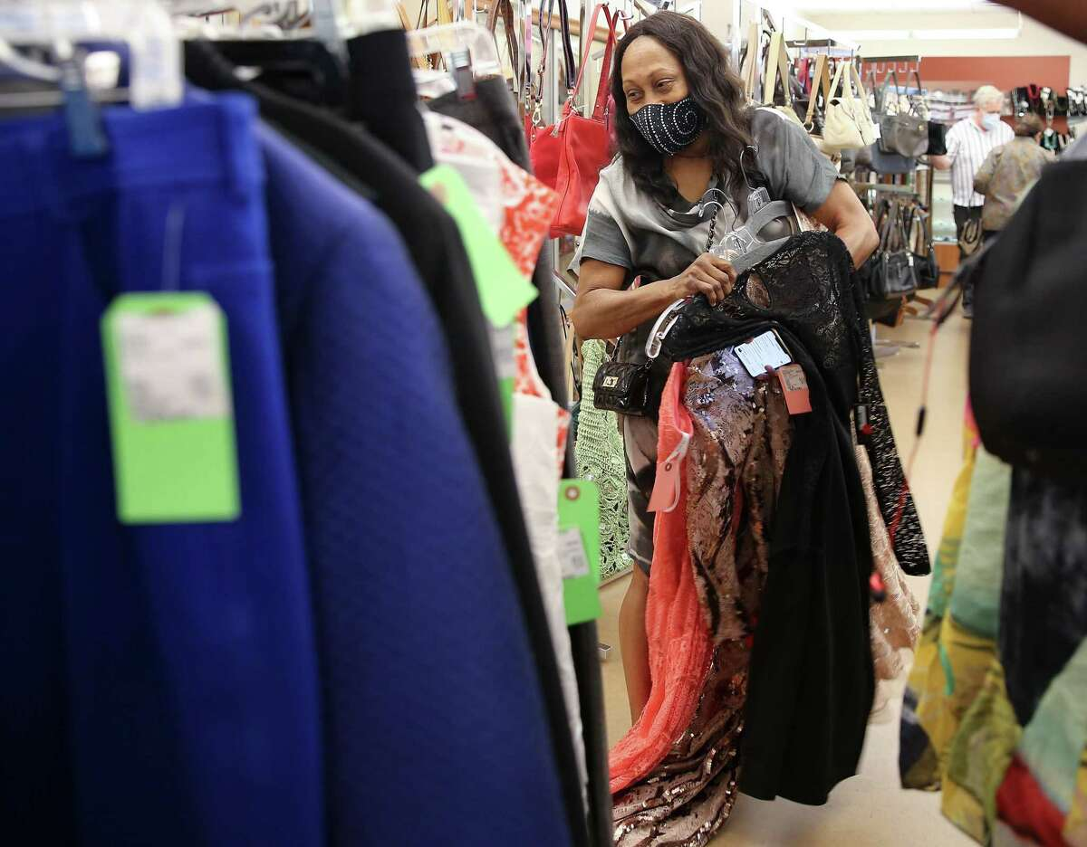 Vanessa Lee holds potential purchases at Charity Guild of Catholic Women Thrift Shop in Houston on Wednesday, Sept. 1, 2021. The organization is celebrating 100 years in October.