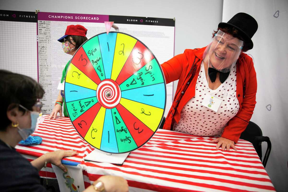 Girl Scout Troop 21 leader Tina Sabuco helps with a ticket prize wheel during the troop's first meeting since the COVID-19 break on Saturday, Sept. 11, 2021.