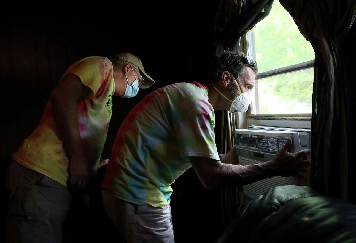"""Volunteers Paulley, left, and Don Grimm install a window unit. """"You see the homeowners and the joy it brings them,"""" Grimm says."""