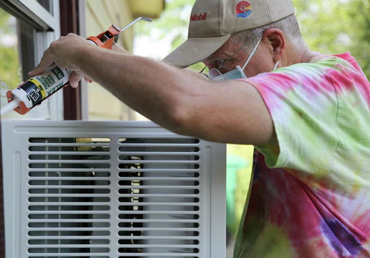 Rebuilding Houston Together volunteer Tom Paulley caulks around a newly-installed window A/C and heat unit at a home in Houston on Wednesday, Sept. 1, 2021.