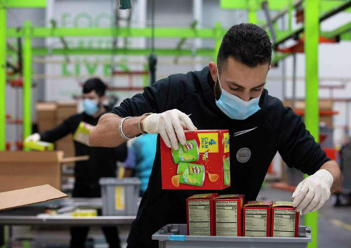 Houston Food Bank volunteer Ali Fawaz sorting while packaging a box of snacks.