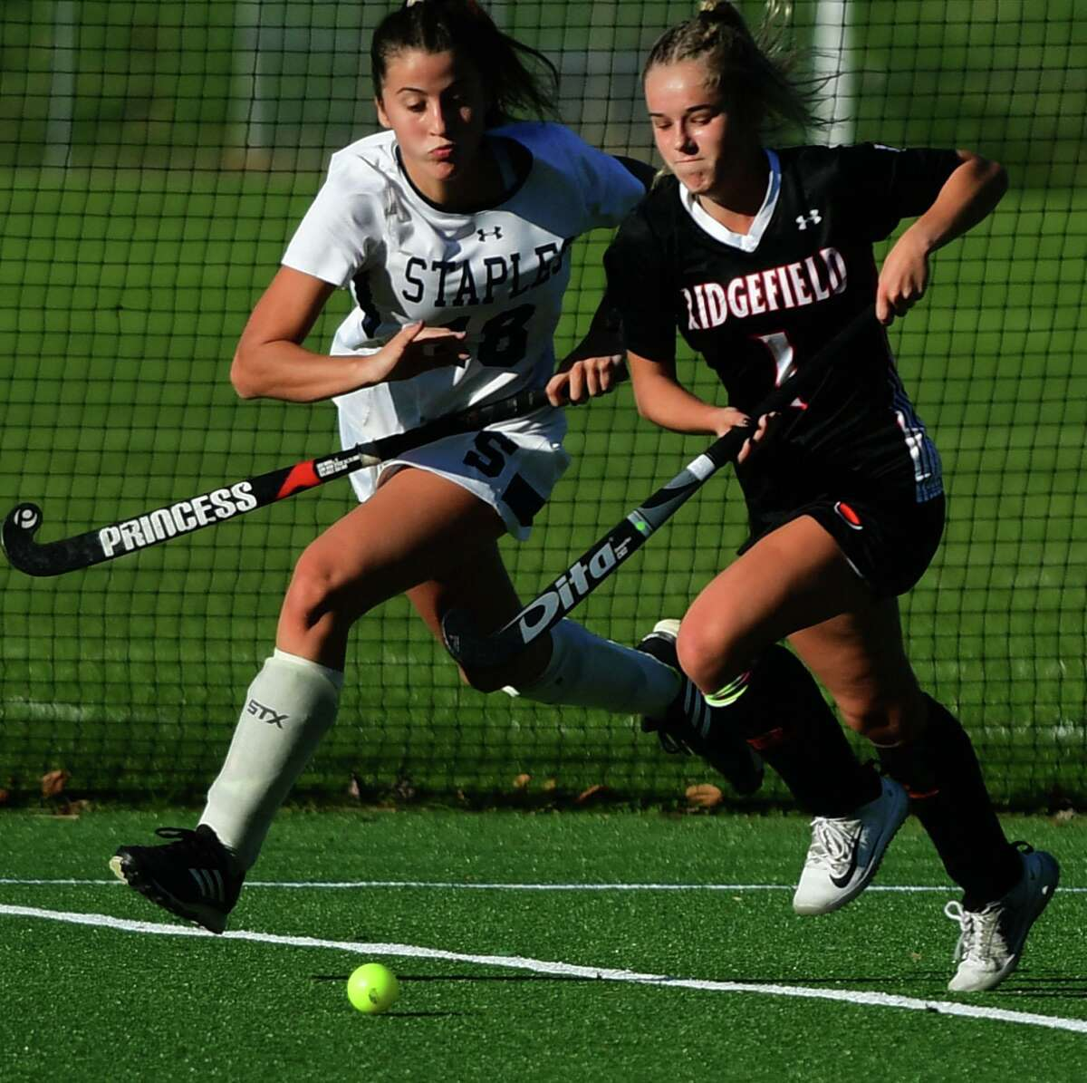 Staples' Olivia Bernard (18) and Ridgefield's Isabel Redrup (1) run for the ball in in their FCIAC Central field hockey championship game on Nov. 10 in Westport.