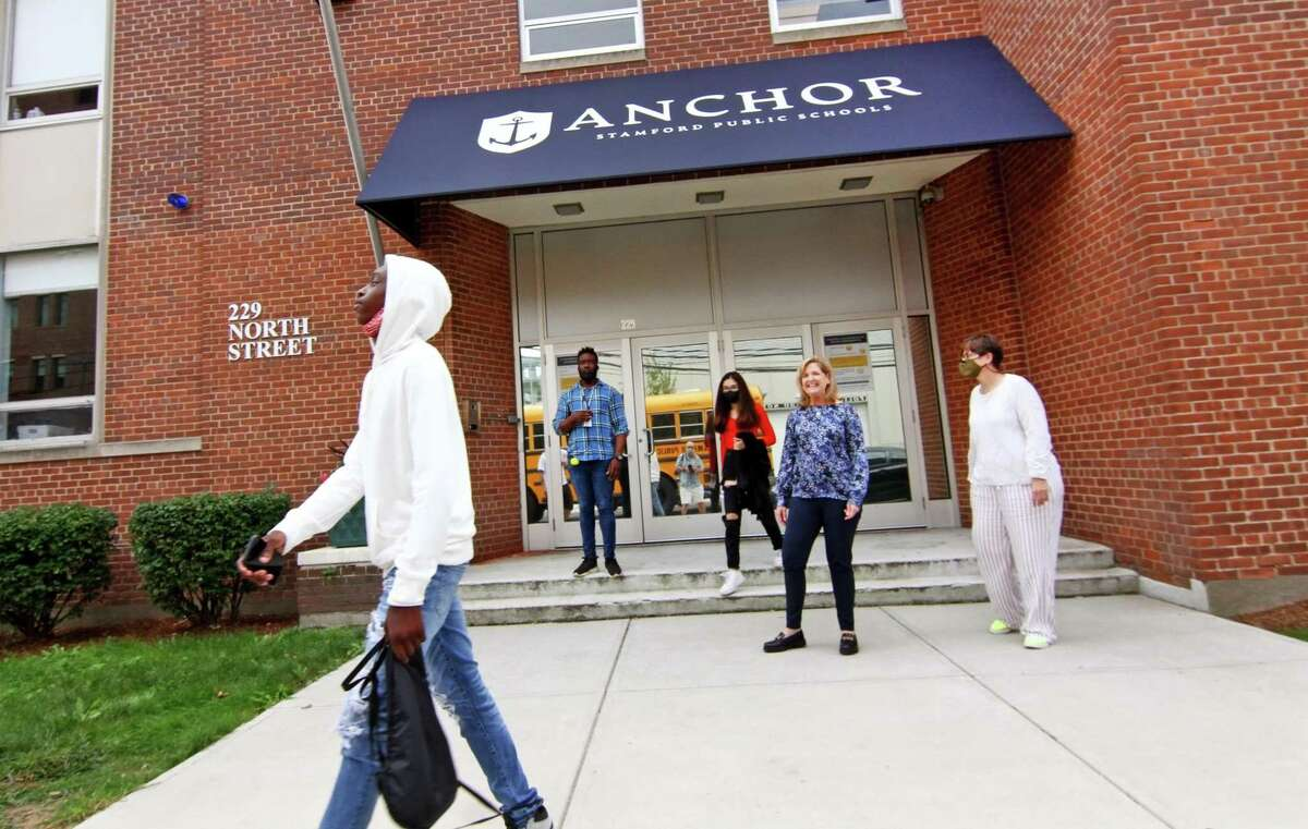 Anchor School Director Laura Greene, in back center, watches as some of her students board the bus in front of the school's new location on North Street in Stamford on Wednesday.