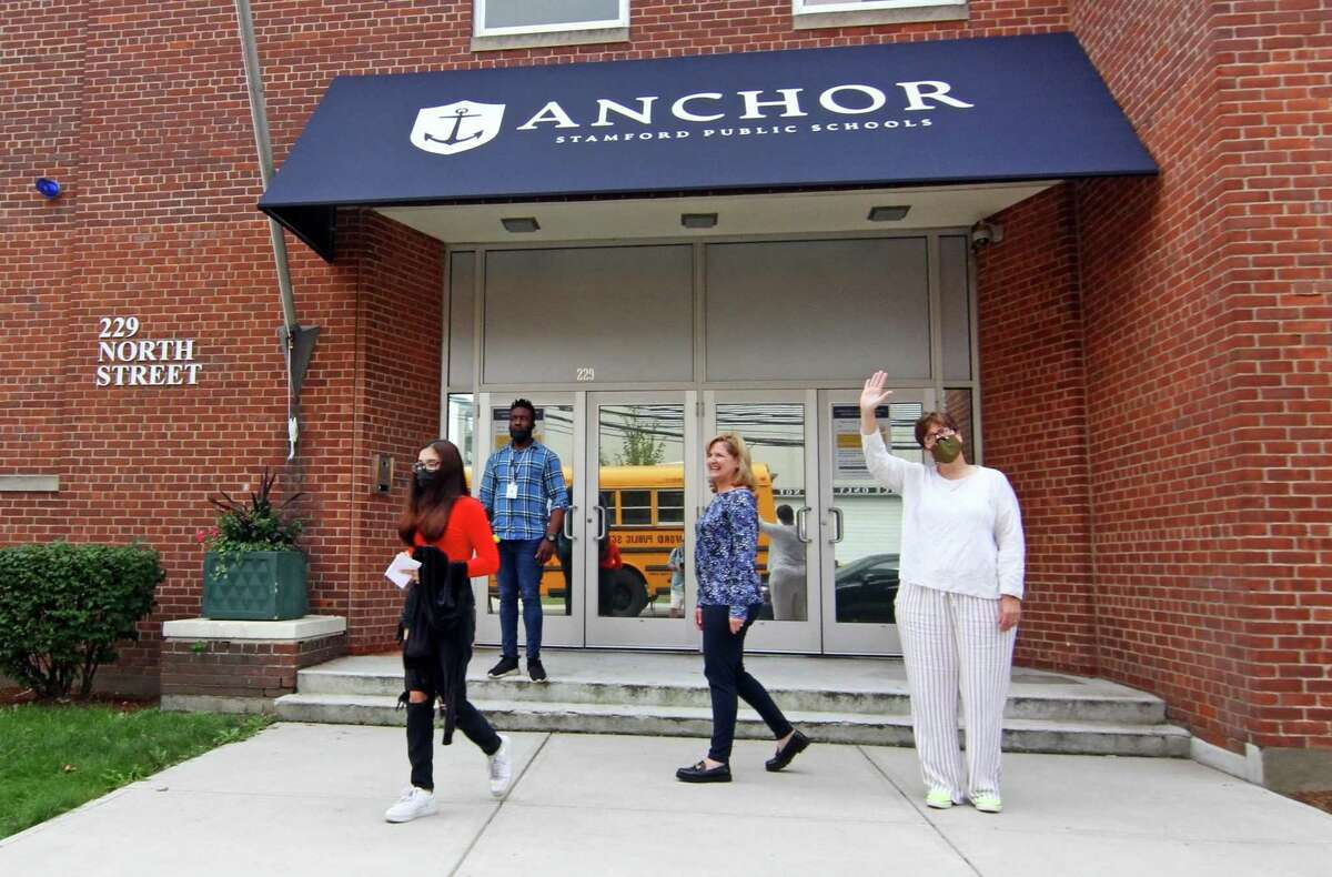 Anchor School Director Laura Greene, in back center, and Jenn Chichester, right, watches as some of their students board the bus in front of the school's new location on North Street in Stamford, Conn., on Wednesday September 22, 2021.