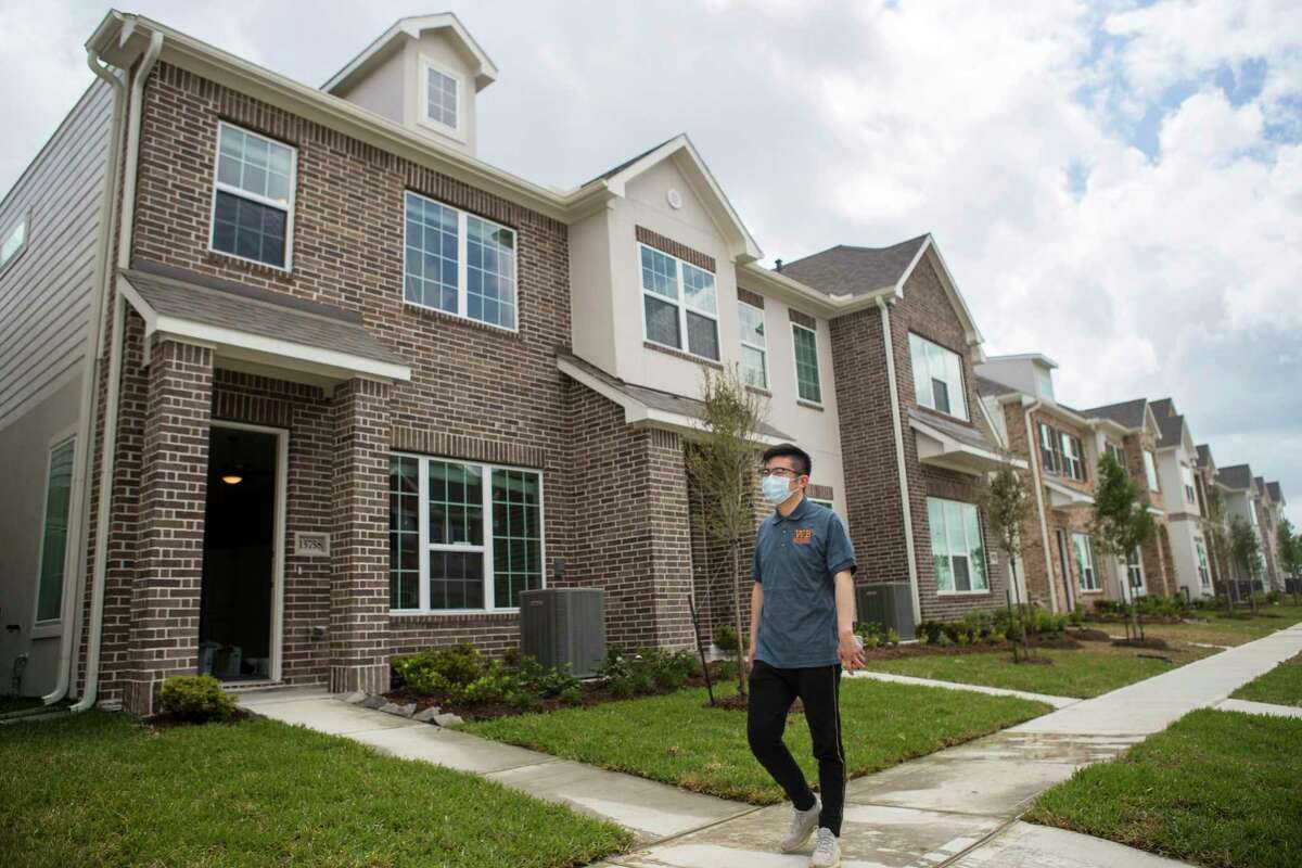 CEO of Wan Bridge Ting Qiao walks past a row of single family townhomes that are completed and ready to lease in the Clearwater at Balmoral subdivision Tuesday, April 6, 2021 in Atascocita. Single-family rentals are drawing increased interest from investors making the bet that people want to live in single-family houses but either will not be able to afford to buy or want to maintain their amenity-rich turnkey lifestyle.