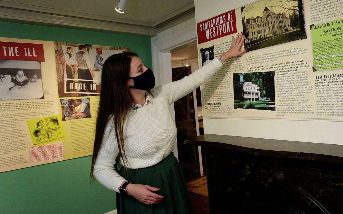 The Westport Museum of History and Culture Director of Programs and Collections Nicole Carpenter points out the new exhibit, Take the Cure, at the museum Wednesday, September 22, 2021, in Westport, Conn. The Westport Museum of History and Culture will be reopening next week with new exhibits after being closed since March 2020.
