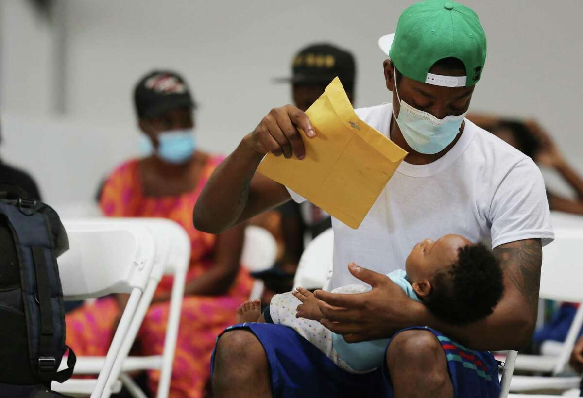 A young migrant is cooled off by his father at a temporary shelter in Houston on Tuesday, Sept. 21, 2021.