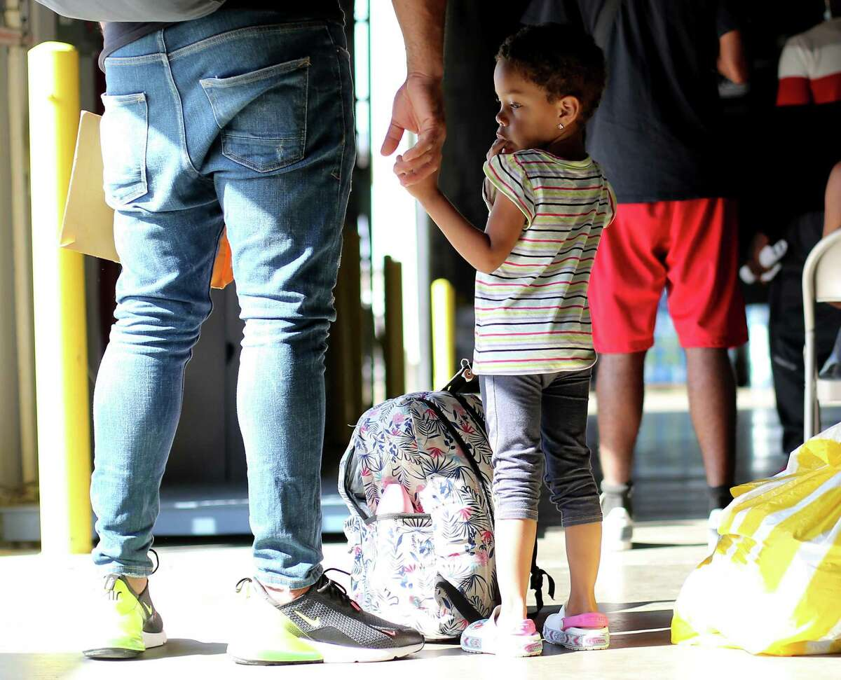 Nicola Peña, 2, of Dominican Republic, holds her dad's hand as they wait in line for medical evaluation at a shelter and transportation hub for migrants in Houston on Tuesday, Sept. 21, 2021.