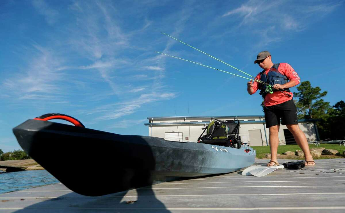 """David Coker, puts fishing poles into kayak for a morning of fishing on Lake Woodlands on the first day of fall, Wednesday, Sept. 22, 2021, in The Woodlands. """"This is the perfect weather for fishing,"""" Coker said. """"The fish should really start to bite as this cooler weather comes through, but even if we walk away with nothing, it's been a great day. How can you complain with weather like this?"""" The first cool front move through the region Tuesday evening and fall conditions are expected to continue into the weekend with highs in the low-80s and lows in the 50s."""