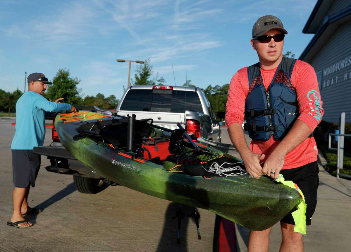 """David Coker, right, gets help moving his kayak toward Lake Woodlands from his friend Alex for a morning of fishing on the first day of fall, Wednesday, Sept. 22, 2021, in The Woodlands. """"This is the perfect weather for fishing,"""" Coker said. """"The fish should really start to bite as this cooler weather comes through, but even if we walk away with nothing, it's been a great day. How can you complain with weather like this?"""" The first cool front move through the region Tuesday evening and fall conditions are expected to continue into the weekend with highs in the low-80s and lows in the 50s."""