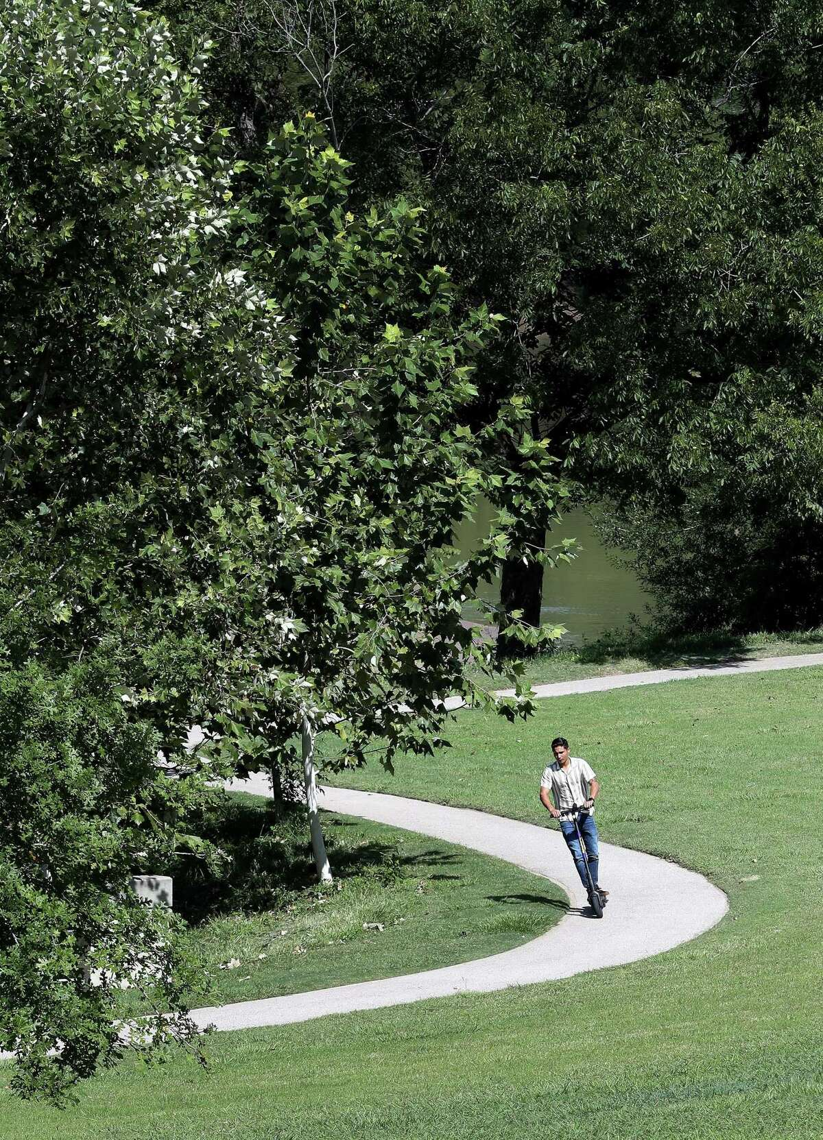 A man on a scooter rides in Eleanor Tinsley Park near Buffalo Bayou, Wednesday, September 22, 2021, in Houston.