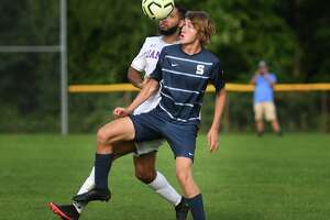 Danbury's Naidson Macedo and Staples' Wiill Adams compete for a header during their FCIAC boys soccer game at Staples High School in Westport, Conn. on Wednesday, September 22, 20i21.