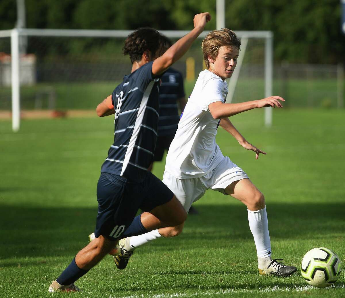 Danbury's Noah Fagan works the ball upfield defended by Staples' Murilo Moreno during their FCIAC boys soccer game at Staples High School in Westport, Conn. on Wednesday, September 22, 20i21.
