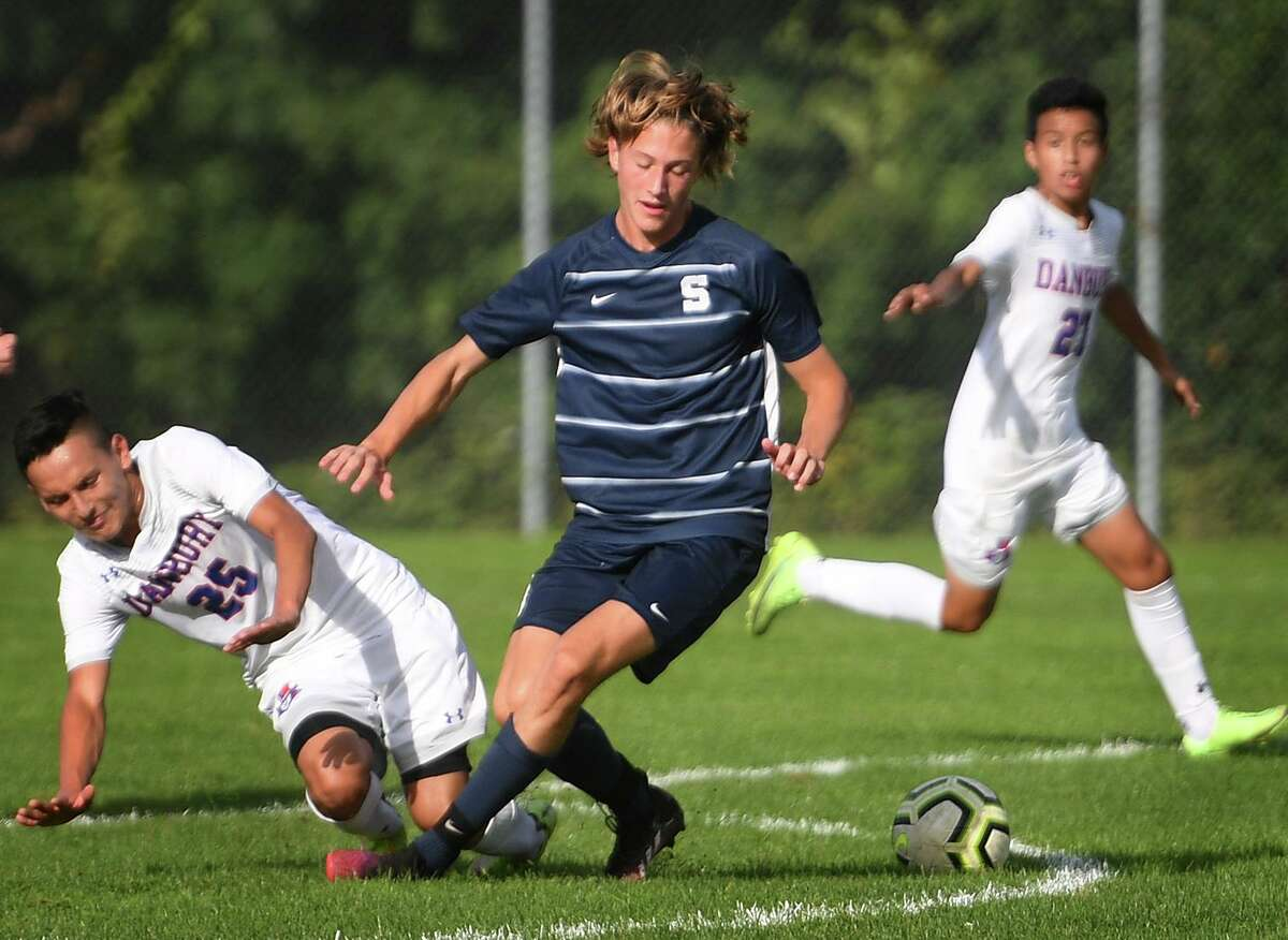 Danbury's Marlon Orellana, left, and Staples' Jaden Mueller compete for the ball at midfield during their FCIAC boys soccer game at Staples High School in Westport, Conn. on Wednesday, September 22, 20i21.