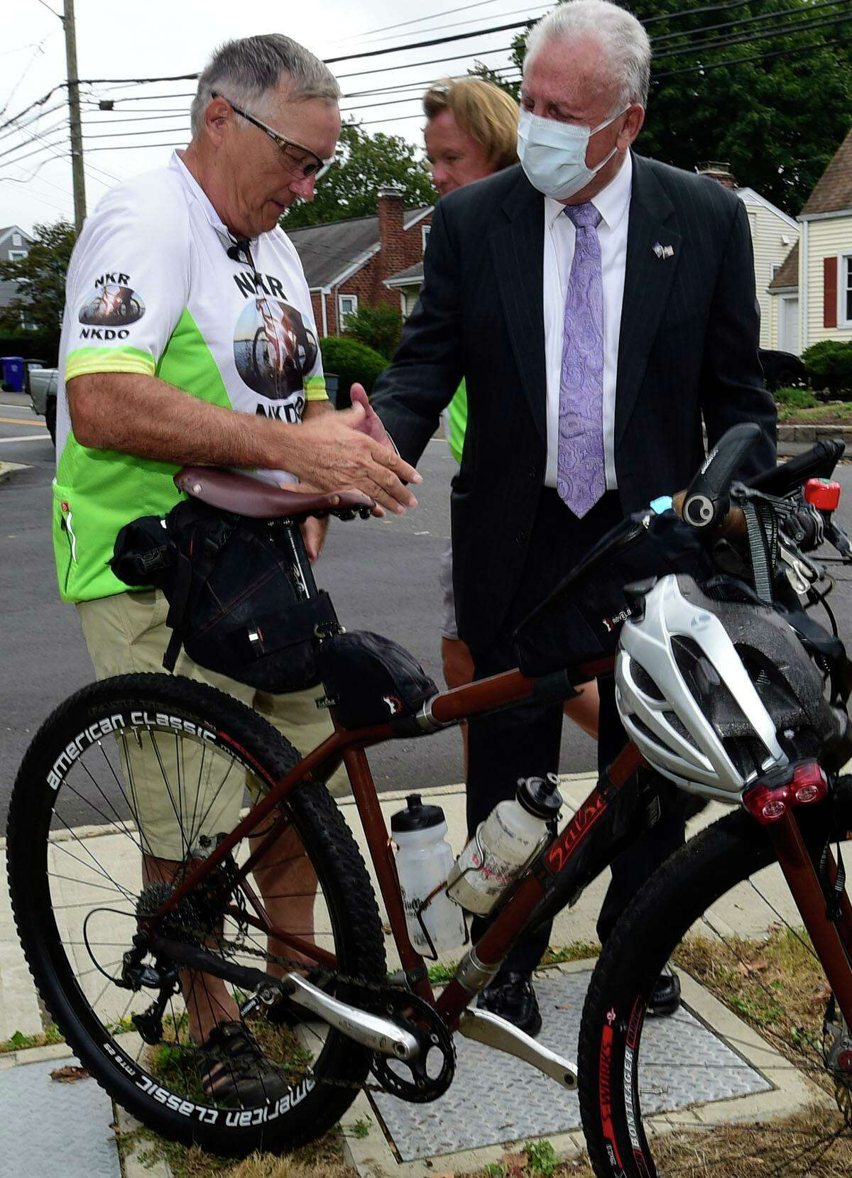"""Kidney donor Mark Scotch meets with Norwalk Mayor Harry Rilling September 19, 2021, along Winfield Street in Norwalk, Conn. Scotch, age 65, is once again hit """"The Organ Trail,"""" cycling his way 1,600 miles to promote kidney disease awareness, living donor need, and post-donation functionality with a marathon bike ride from Martha's Vineyard, Massachusetts to his home in Plover, Wisconsin."""