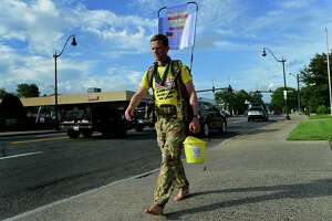 British Army Major Chris Brannigan walks barefoot along West Avenue in his journey from Maine to North Carolina on Wednesday in Norwalk. Brannigan is walking to raise money to help fight his daughter's rare illness.