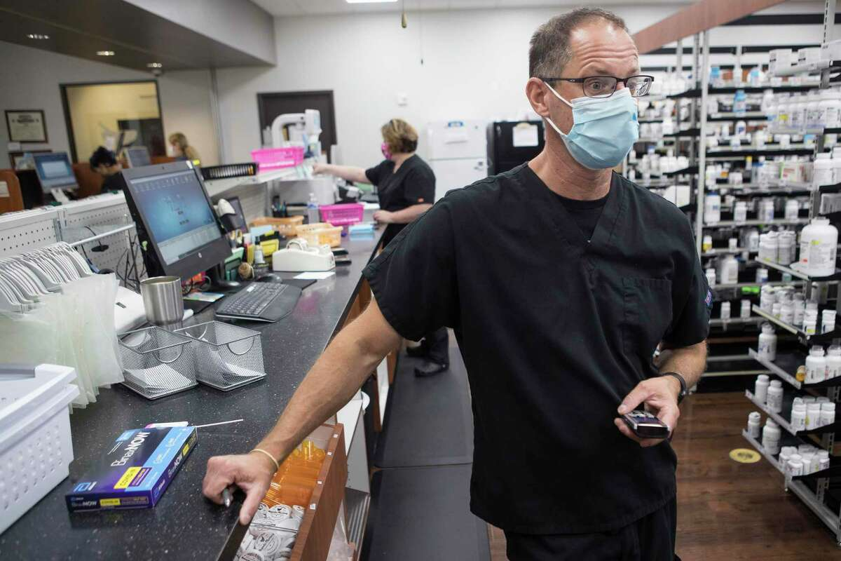 A completed BinaxNOW COVID-19 Antigen self test is shown on the counter next to pharmacist Steve Hoffart as he works at Magnolia Pharmacy Monday, Aug. 16, 2021 in Magnolia.