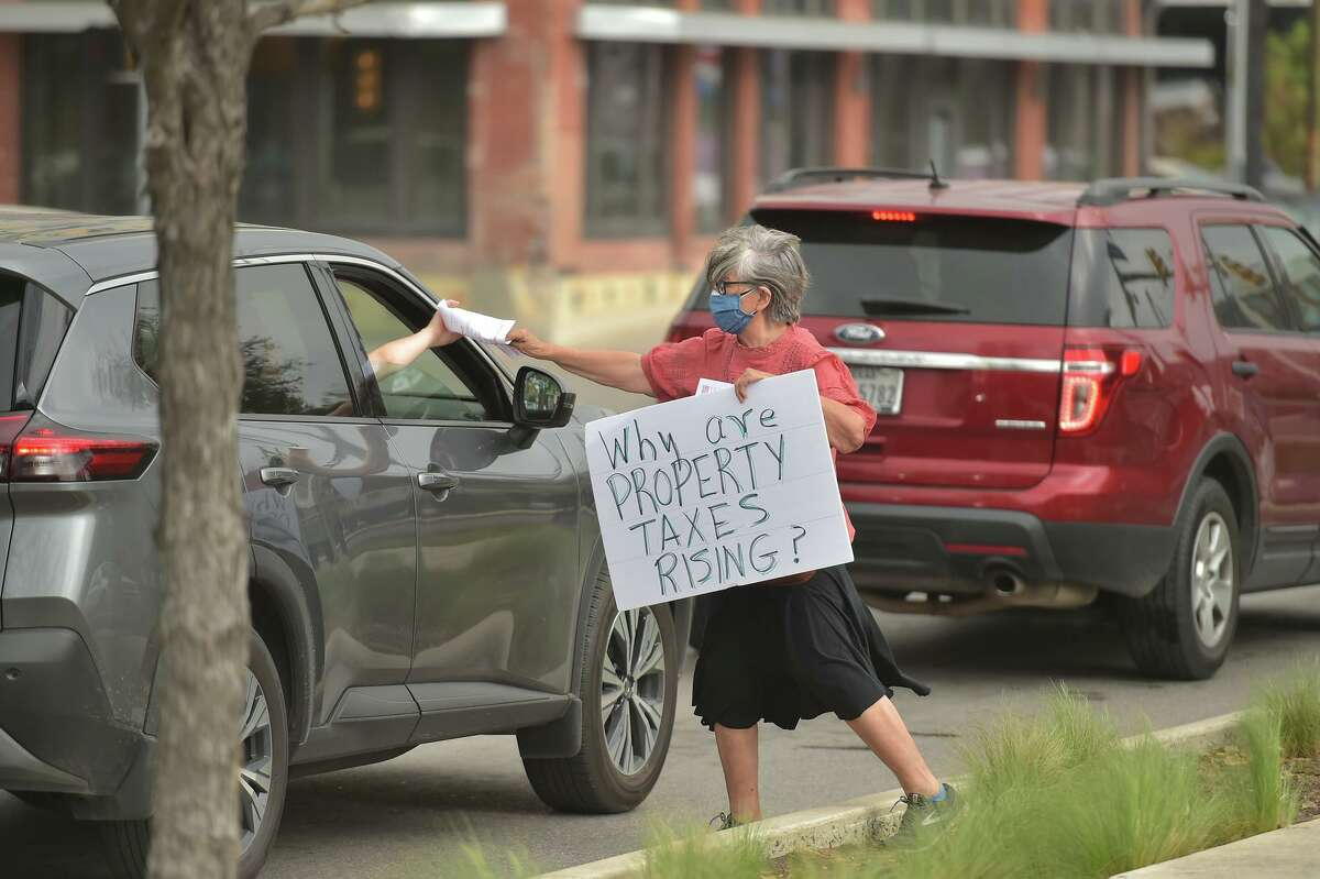 Rebecca Flores hands out literature to a motorist during a protest against rising property taxes and corporations getting tax breaks Saturday at the corner of Flores St. and Cesar Chaver Blvd.