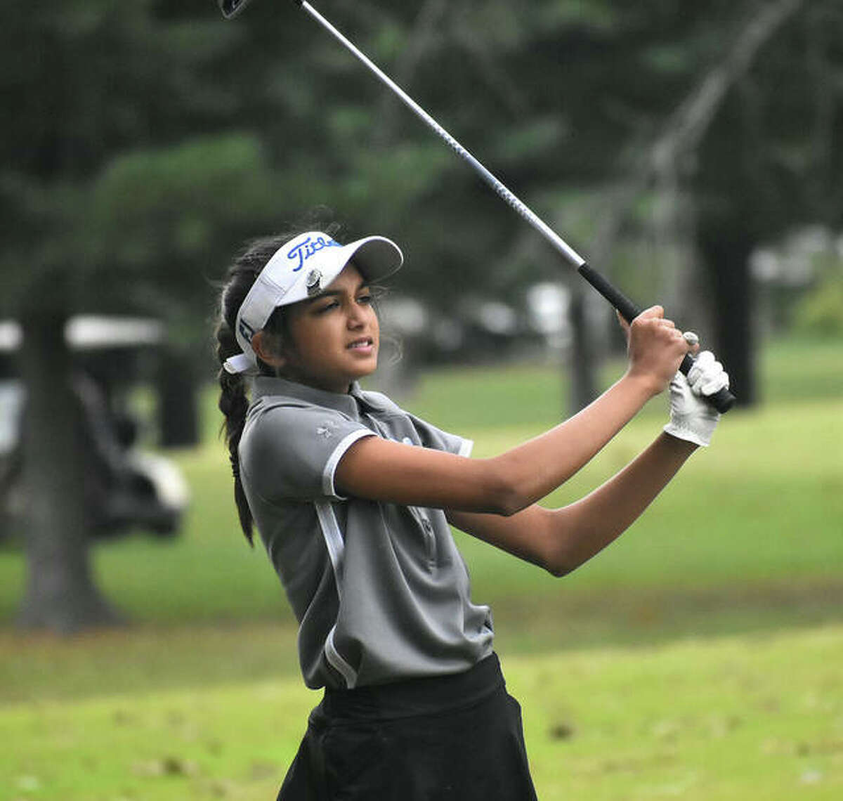 Edwardsville's Ruhee Gupchup watches her second shot on No. 9 at Oak Brook Golf Club during a triangular with Marquette and Triad on Wednesday in Edwardsville.