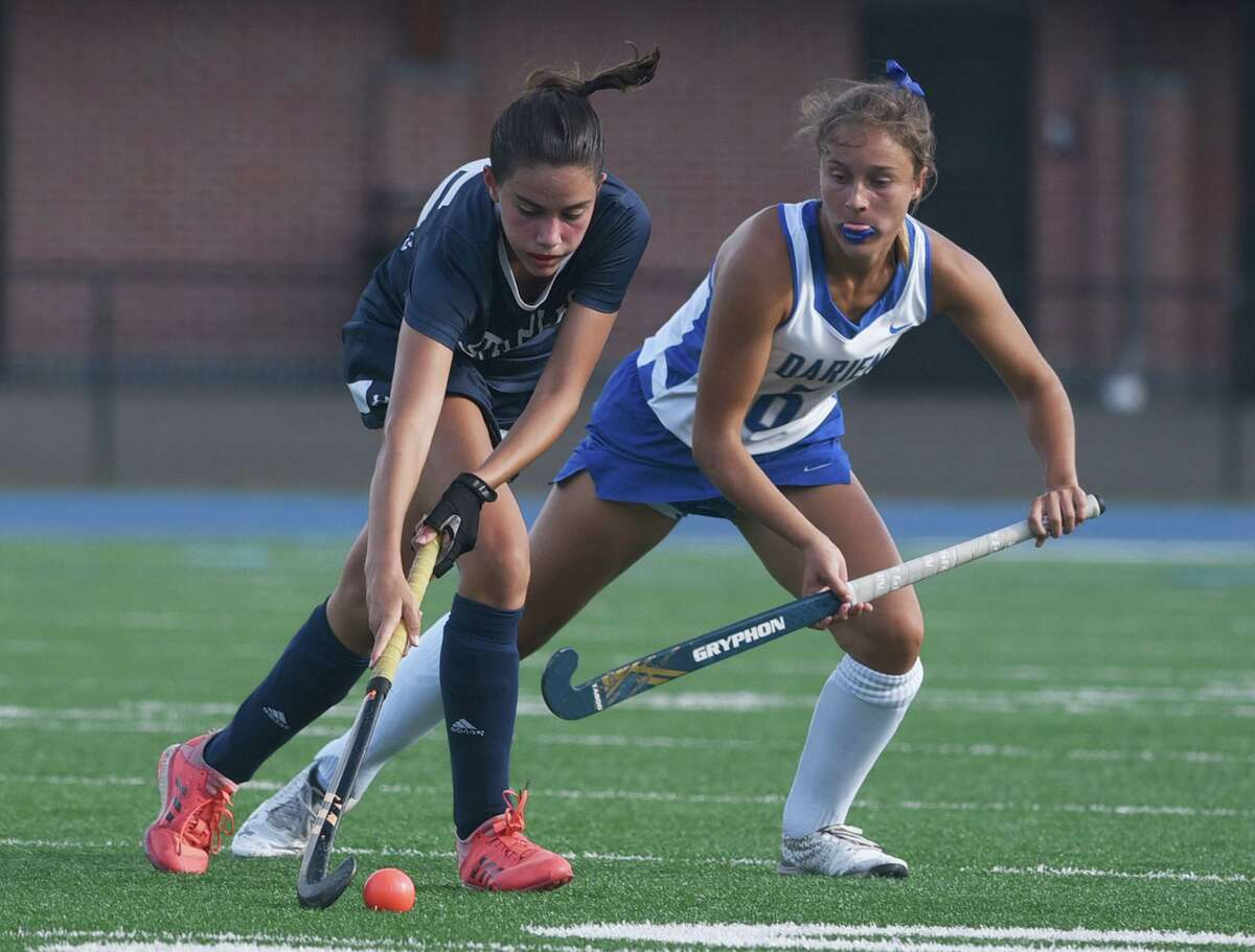 Staples' Sofia Fidalgo-Schioppa (25) plays the ball near midfield, while Darien's Maddy Hult (6) defends during a field hockey game in Darien on Wednesday.