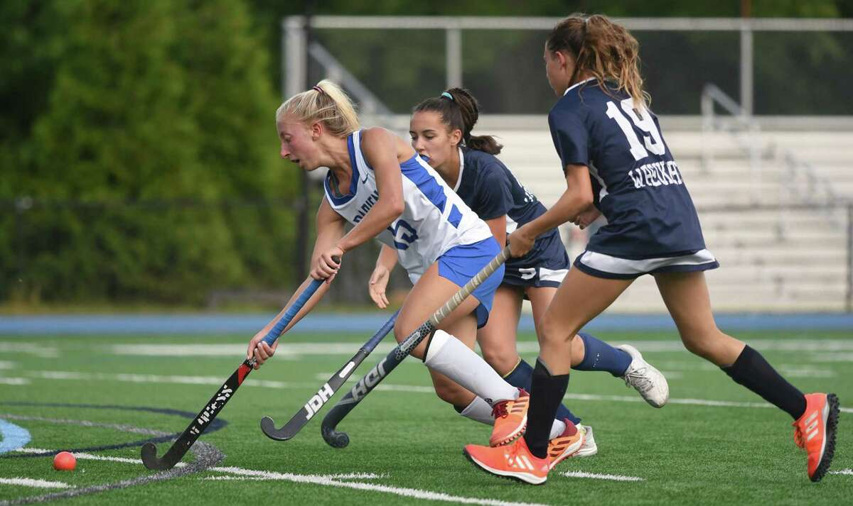 Darien's Kaci Benoit (15) cuts between Staples' Kathryn Asiel (10) and Emma Larit (19) during a field hockey game in Darien on Wednesday, Sept. 22, 2021.