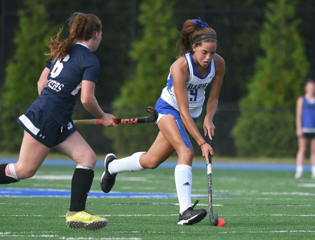 Darien's Raina Johns (9) brings the ball through the midfield while Staples' Isabelle Nahon (6) closes in during a field hockey game in Darien on Wednesday, Sept. 22, 2021.