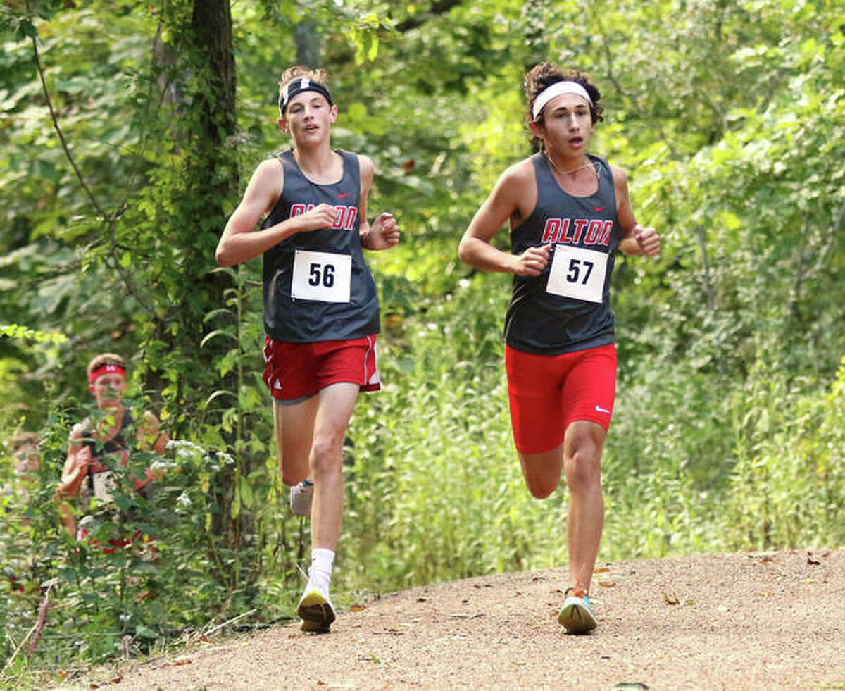 Alton's Parker Mayhew (56) and Alex Macias (57) run through the woods in the opening half-mile of the new 5K course behind Alton High in Godfrey on Wednesday afternoon.