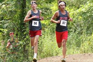 Alton's Lucas Landuyt (56) and Alex Macias (57) run through the woods in the opening half-mile of the new 5K course behind Alton High in Godfrey on Wednesday afternoon.