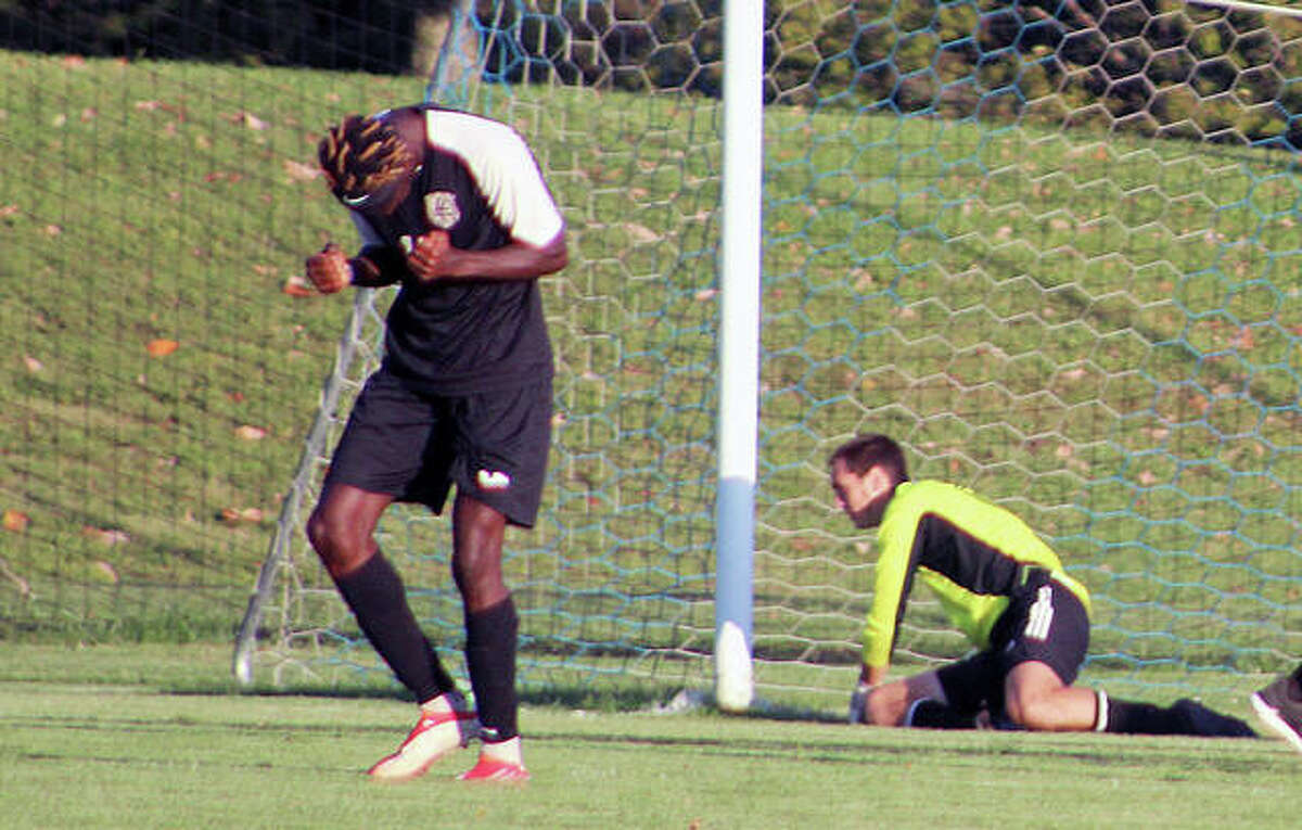 Lewis and Clark's Ridwan Saka, left, pumps his fists in celebration after teammate Cameryon Stewart's successful golden-goal penalty kick got past St. Louis Community College goalie Michael Geary, on the ground, to decide Wednesday's 2-1 overtime win by LCCC at St. Louis Community College at Florissant Valley.