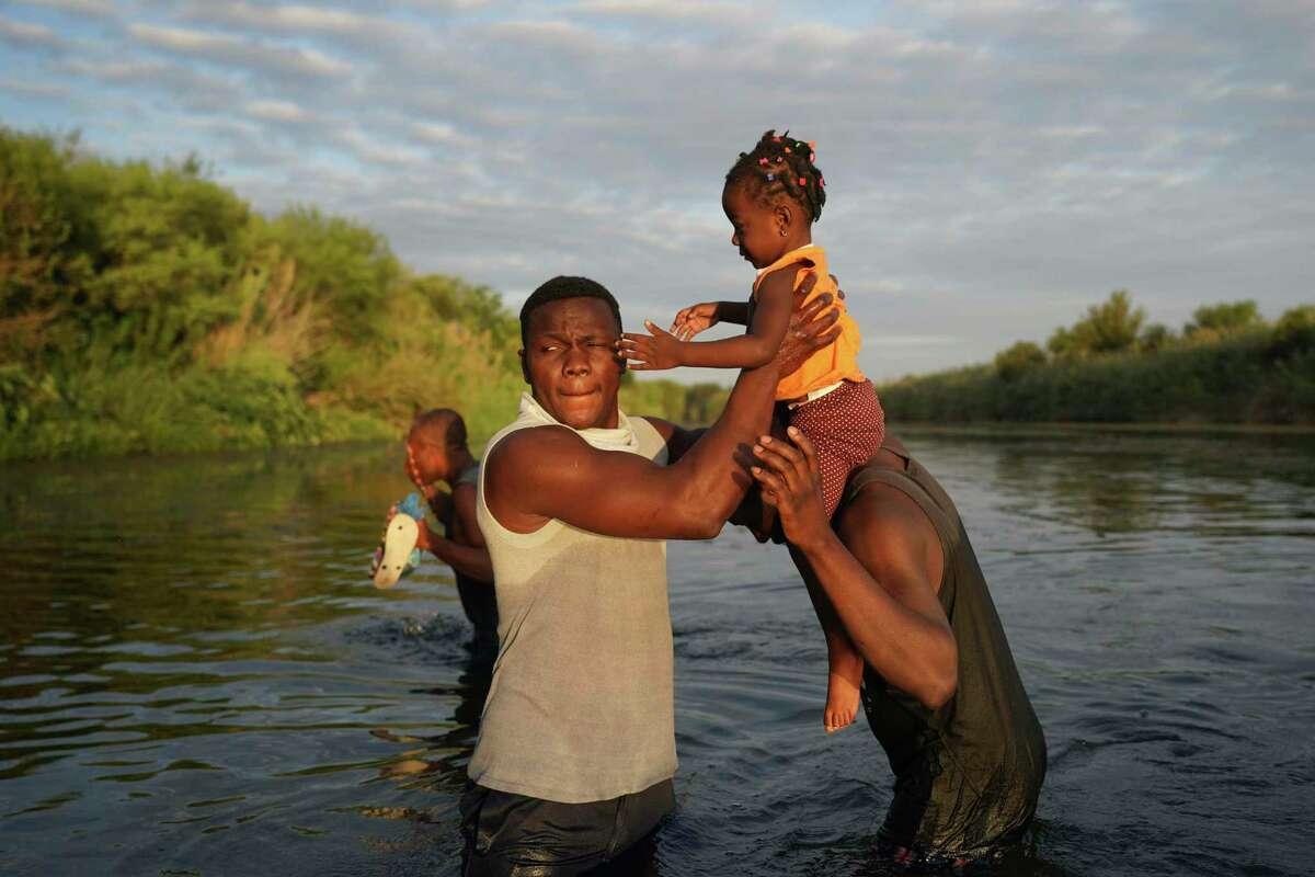 Hombres cargan a una niña a través del Río Bravo mientras los migrantes, muchos de Haití, abandonan Del Río, Texas, para regresar a Ciudad Acuña, México, el miércoles 22 de septiembre de 2021 temprano, algunos para evitar una posible deportación de EEUU otros a conseguir suministros.