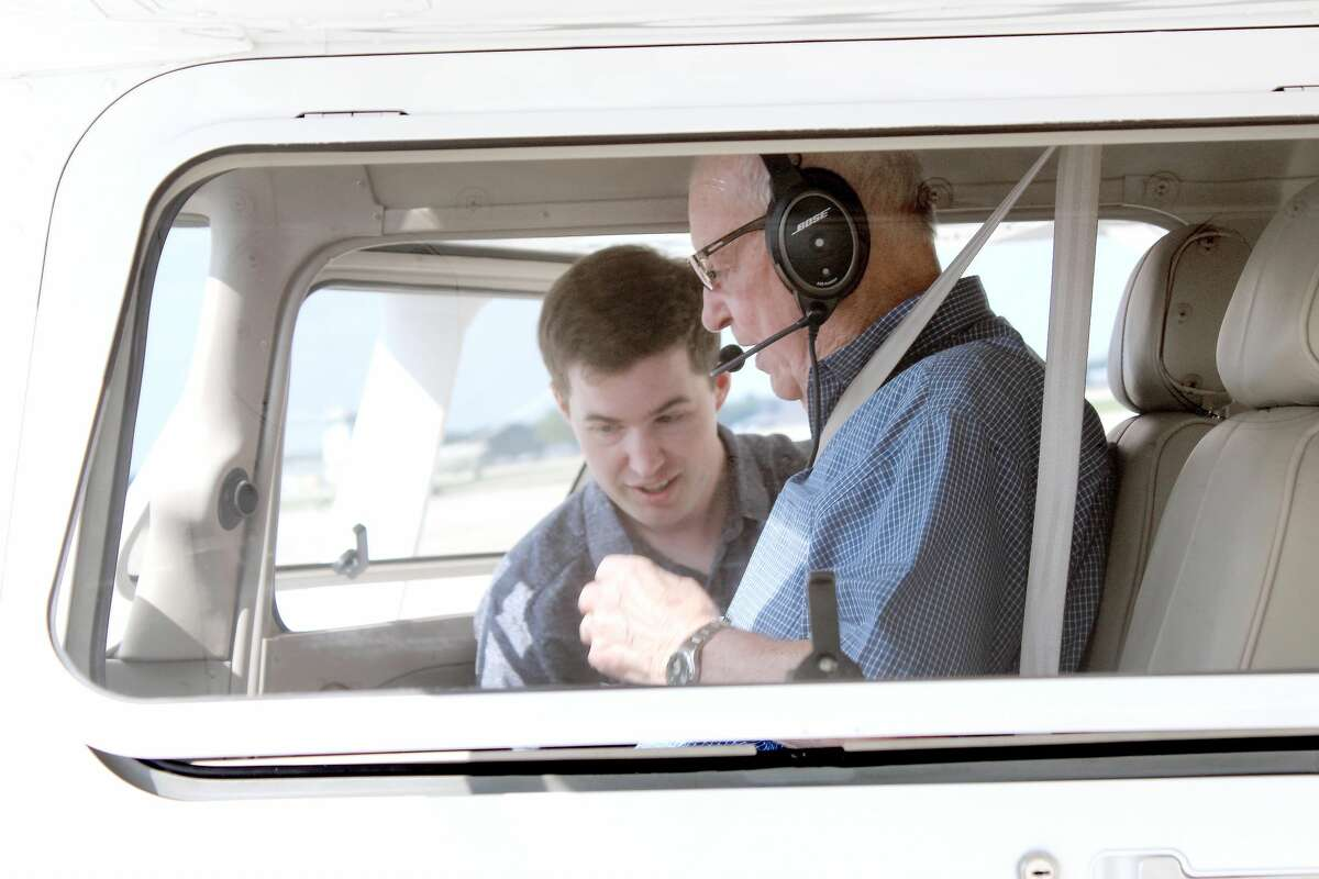 Sean Sperry helps his grandfather Kenneth Sperry get settled and buckled up in a Cessna 172S Skyhawk.
