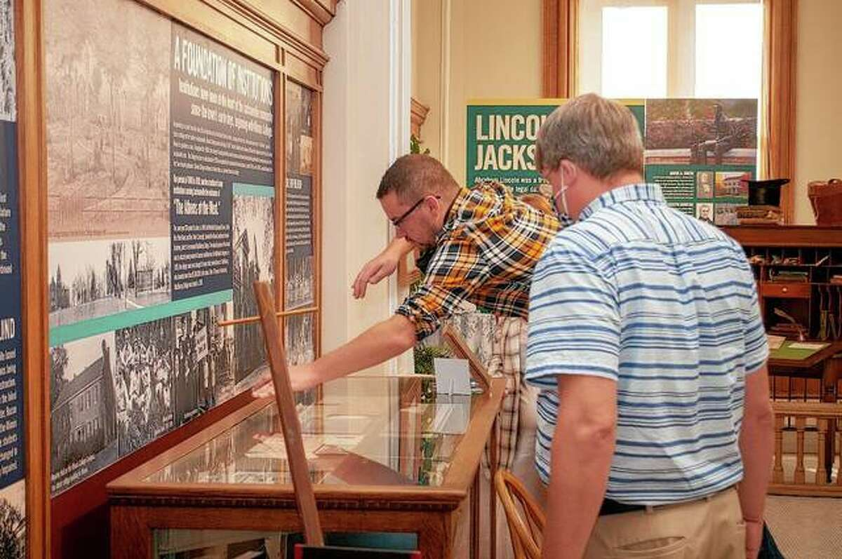 Jacksonville Area Museum board member Nick Little reaches over one of the display counters at the museum.