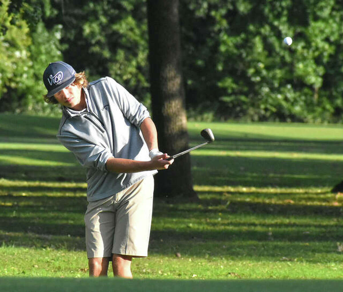 Father McGivney's Brandon Reed hits a chip shot during his round on the east nine at Oak Brook Golf Club on Wednesday in Edwardsville.