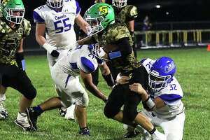 Southwestern's Gavin Day runs through a pair of Greenville tacklers during the Birds' 28-27 SCC football victory last Friday at Hauser Field in Piasa.