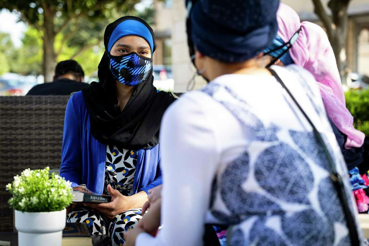 Fatimah Ali chats with her sisters at a shopping area on Saturday, Sept. 18, 2021.