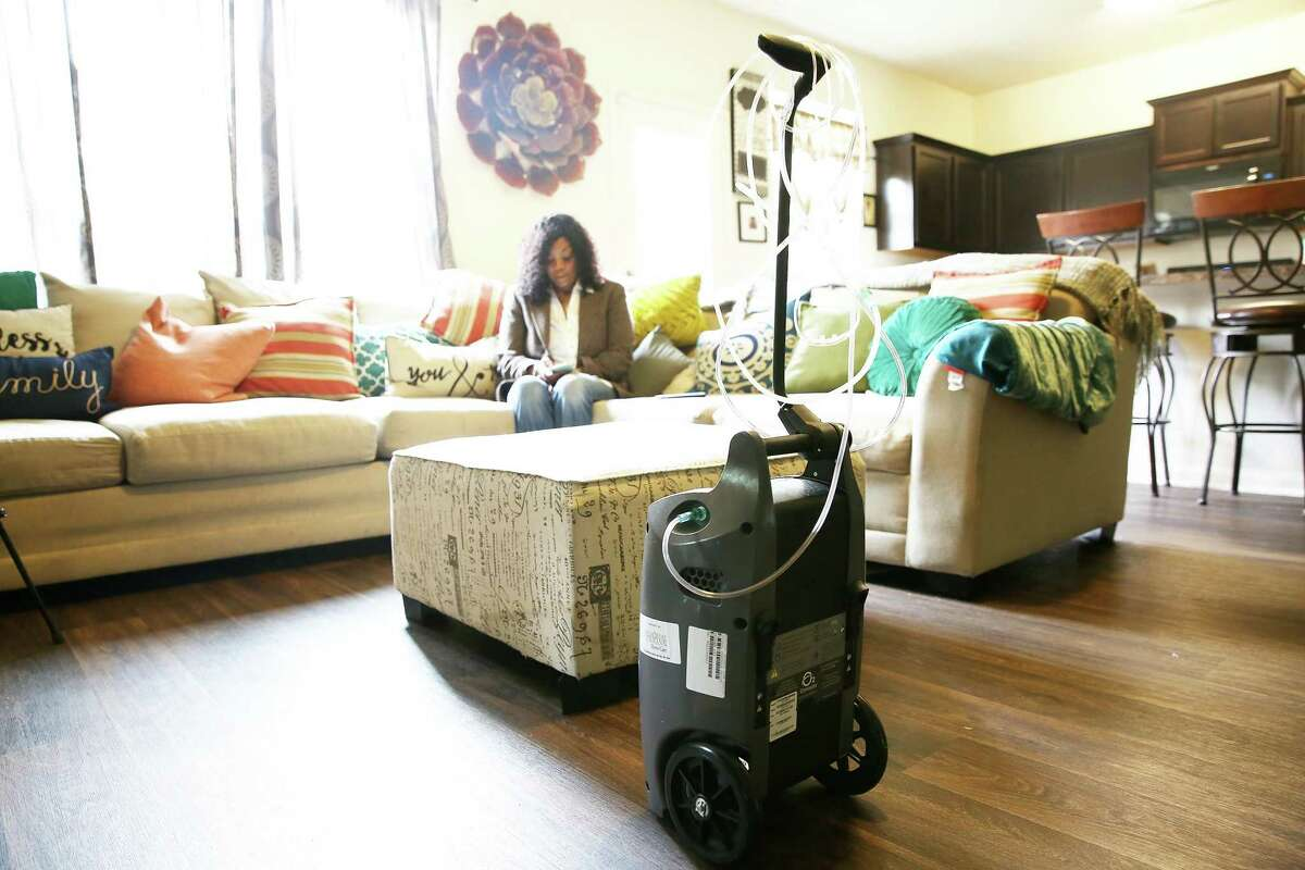An oxygen machine sits in Michelle Tate's living room in Houston on Thursday, Sept. 16, 2021. Tate needed the machine for months after she left the hospital from a COVID.