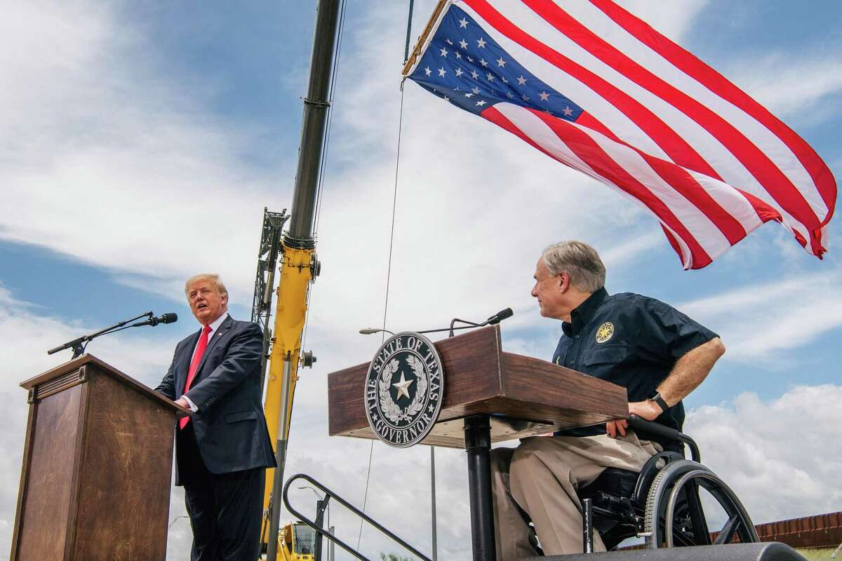 Texas Gov. Greg Abbott, right, listens to former President Donald Trump's address during a tour to an unfinished section of the border wall on Wednesday, June 30, 2021, in Pharr, Texas. (Brandon Bell/Getty Images/TNS)