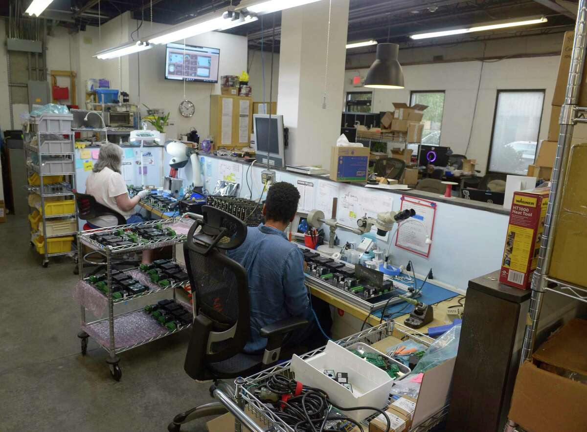 Employees assemble circuit boards for JuiceBar EV chargers at Gyre9. The company is relocating its business from Oxford to a larger space in Southbury, where it can increase production and hire more workers. Thursday, September 23, 2021, Oxford, Conn.