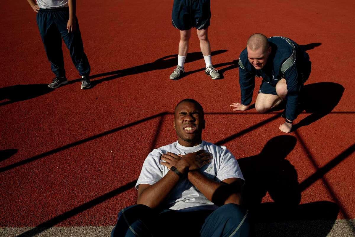 Airman trainee Robert Harris at Joint Base San Antonio-Lackland finishes his sit up requirements for the final PT test while his wingman Ian Peskar keeps count during basic training last March.