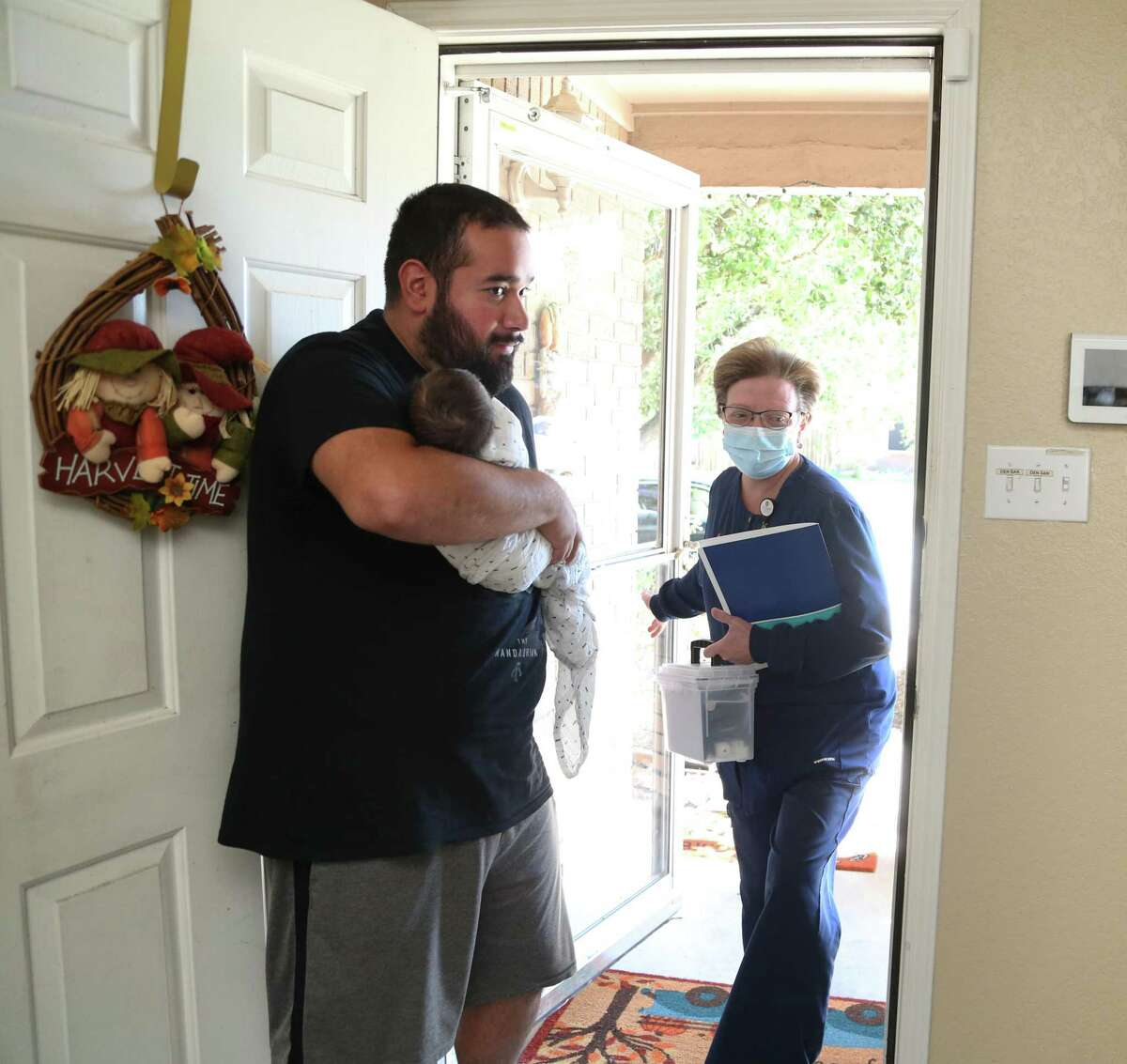 Isaiah Miranda, 28, holds his newborn child, Kaissen Miranda, as nurse Melanie Baker visits to check on the mother, Bridney Hernandez, at their home in San Antonio as part of a new University Health initiative called Hospital at Home.