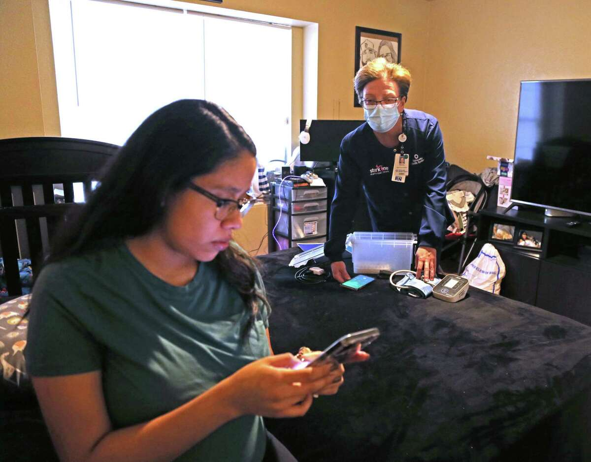 Nurse Melanie Baker, right, helps Bridney Hernandez prepare for a video call with her doctor as part of a new University Health initiative called Hospital at Home.