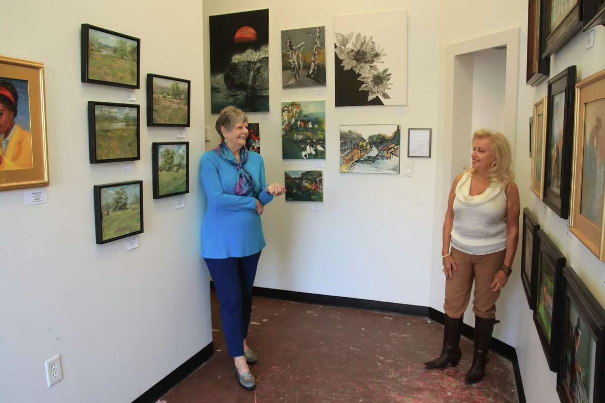 """Margo Green, left, and Naomi Stevens pause while preparing the Pearland Arts League's first gallery of its own, which will be at the Pearland Town Center. """"It's been exciting, invigorating, and exhausting and so rewarding,"""" said Stevens, the group's president."""