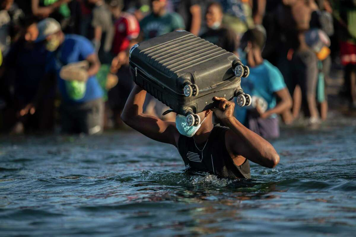 Migrants, many from Haiti, wade across the Rio Grande from Del Rio, returning to Ciudad Acuña, Mexico, on Monday, to avoid deportation. President Joe Biden's policies have signaled the border is open.